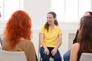 Meeting of support group. Happy woman talking about her life, everything good. Mental health, psychotherapy concept