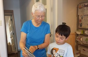 A grandmother and a little boy looking at a picture book